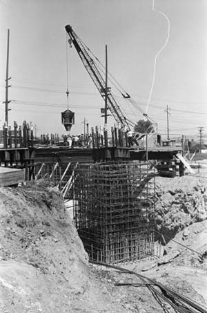 Workers using concrete bucket to pour Space Needle foundation - circa May 1961