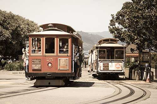 Two cable cars driving on tracks